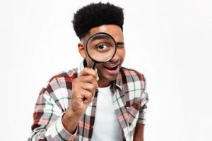 Portrait of a cheerful young african man looking through magnifying glass isolated over white background